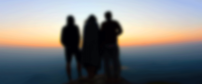 3 people stood on top of a mountain